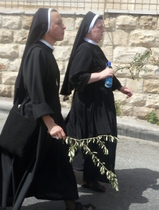 Nuns carrying palm leaves