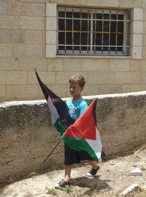 Nabi Saleh boy carries Palestinian flag
