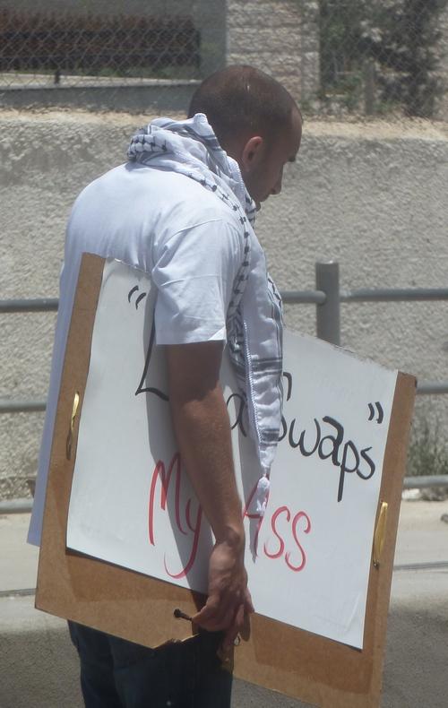 """Ung demonstrant bærer skiltet med """"landswaps my ass"""""""