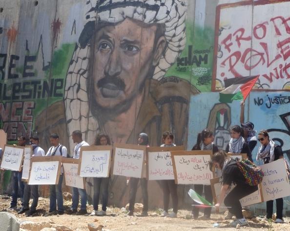 Unge med skilte stiller op til billeder før søndagens Naksa-demonstration